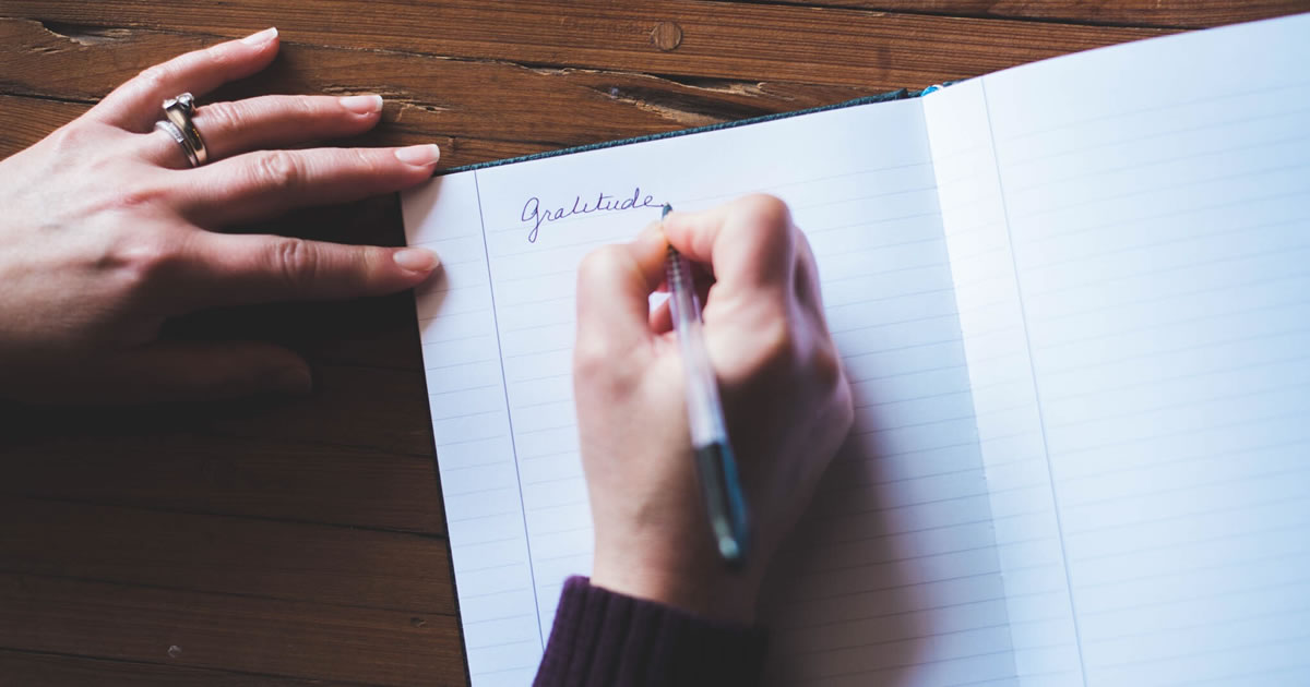 Woman writing in gratitude journal at desk