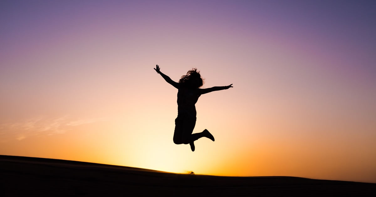 Silhouette of happy woman jumping for joy with colorful sunset