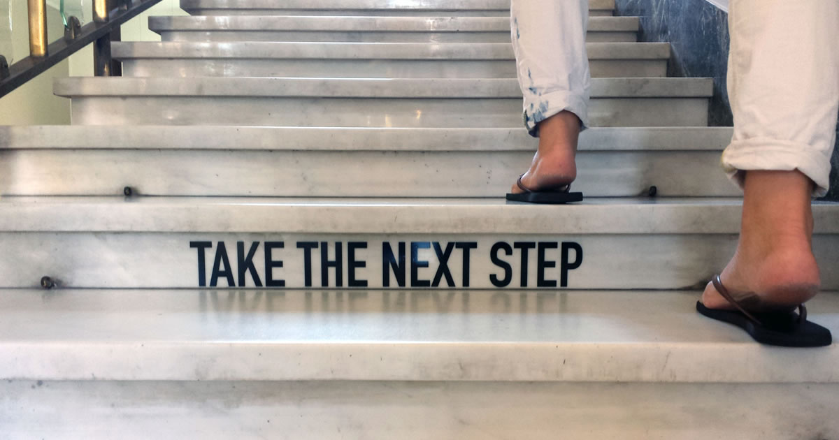 Take the next step; woman walking up stairs