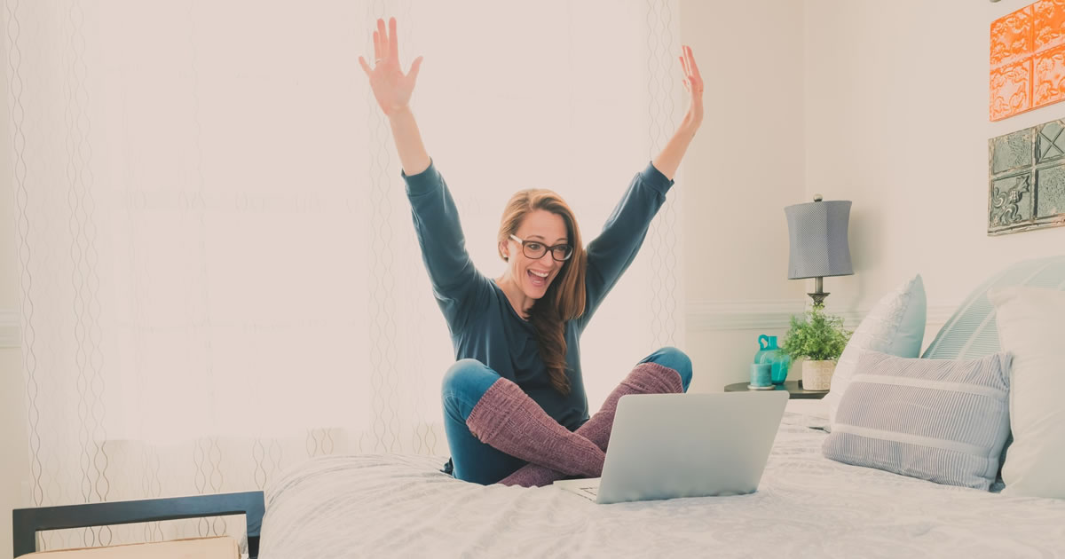 Excited woman using laptop computer