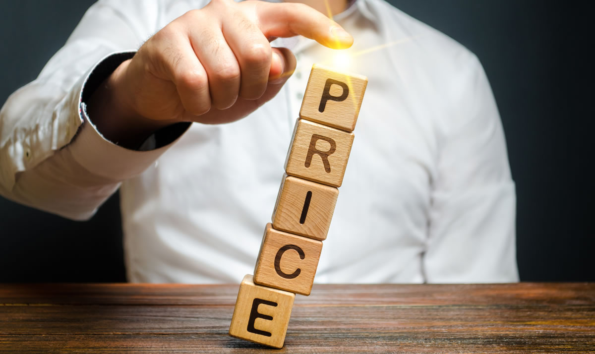 Businessman balances blocks that spell PRICE using his finger
