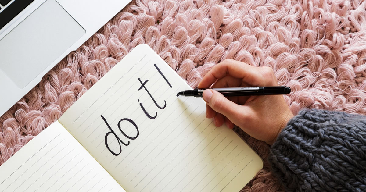 "Laptop next to a hand writing ""Do it!"" in black pencil in a notebook, on pink background"