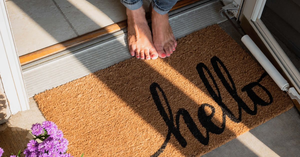 Woman's bare feet standing in doorway of home by a welcome mat with the word hello