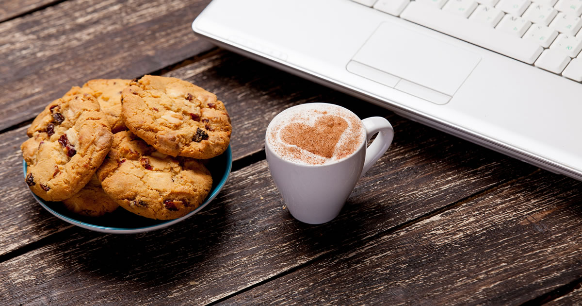 Plate of cookies, laptop, and cup of coffee with a milk heart symbol, all on a brown wooden background
