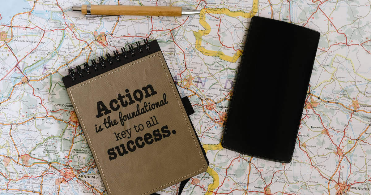 Lay flat of map, notebook with motivational quote: Action is the foundational key to all success