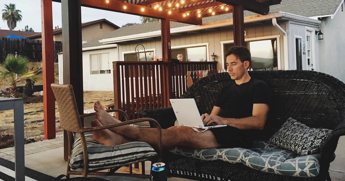 Writer working from home on his laptop in a comfortable backyard