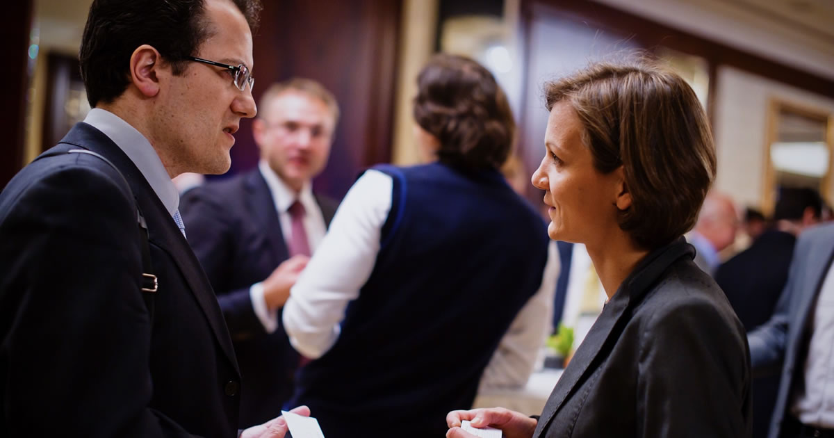 Business professionals exchanging business cards at a networking event