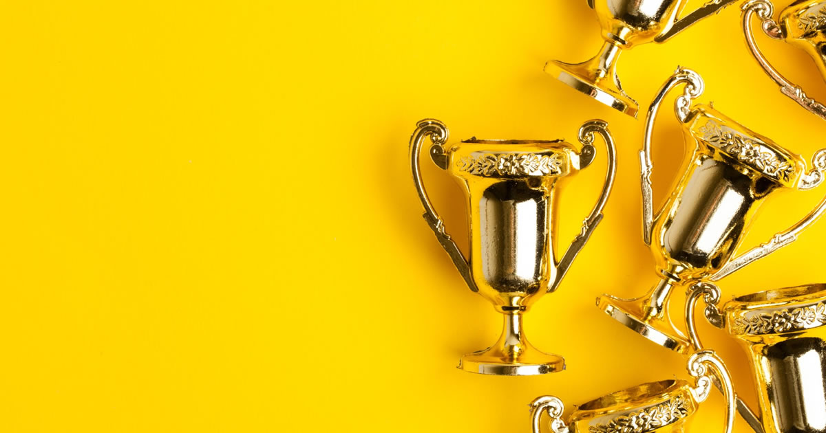 Gold winners trophies on a bright yellow background