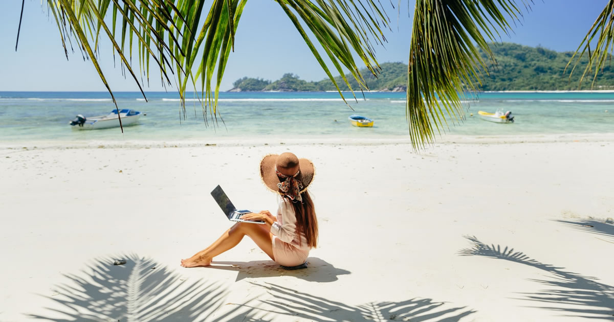 Woman typing on a laptop while sitting on the sand at the beach