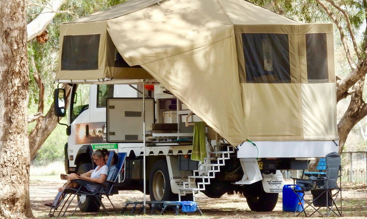 Andrew and Peta Murray relaxing outside their truck camper in the Australian Outback