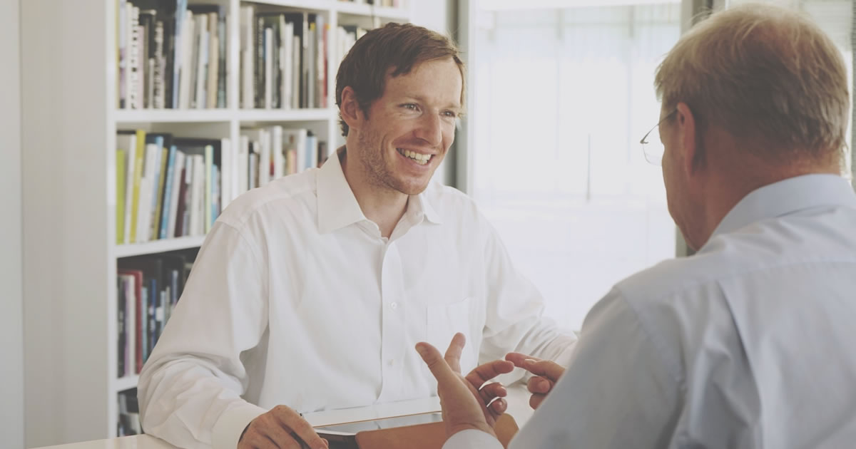 Two businessmen smiling and talking in office library setting