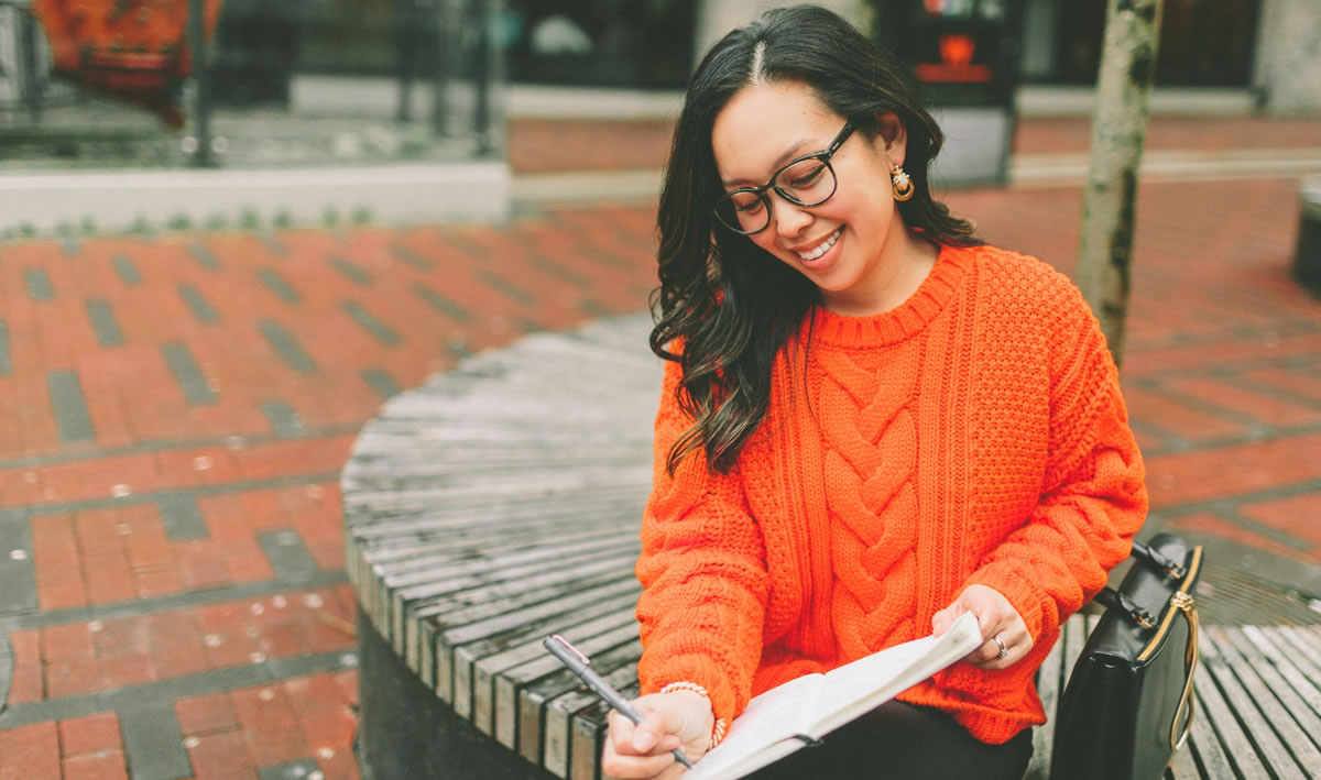 Smiling woman writing in a notebook while sitting in an outdoor urban setting