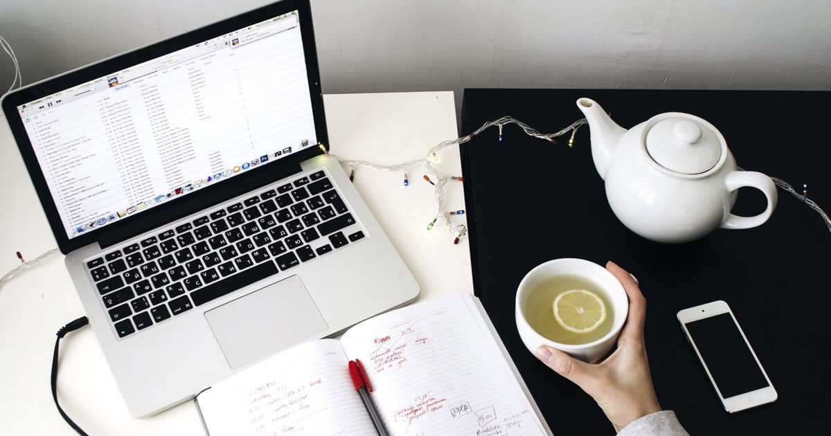 Overhead photo of desk with laptop, paper notebook, mobile phone, and person's hand holding a cup of tea