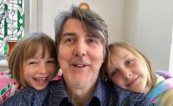 Gordon and his two smiling daughters in quarantine at home