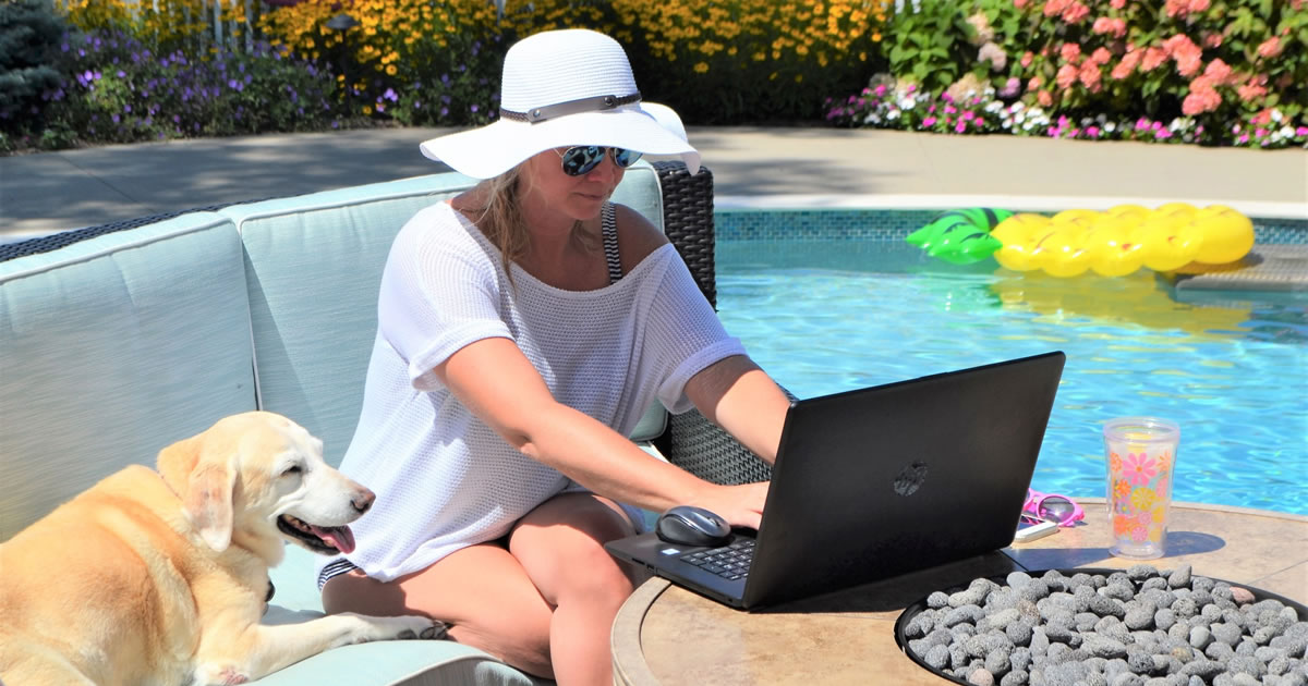 Woman sitting outside by pool using laptop with dog next to her