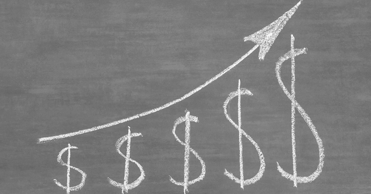 Chalkboard with drawing of dollar signs increasing in size beneath an upward sloping arrow, symbolizing growth in income
