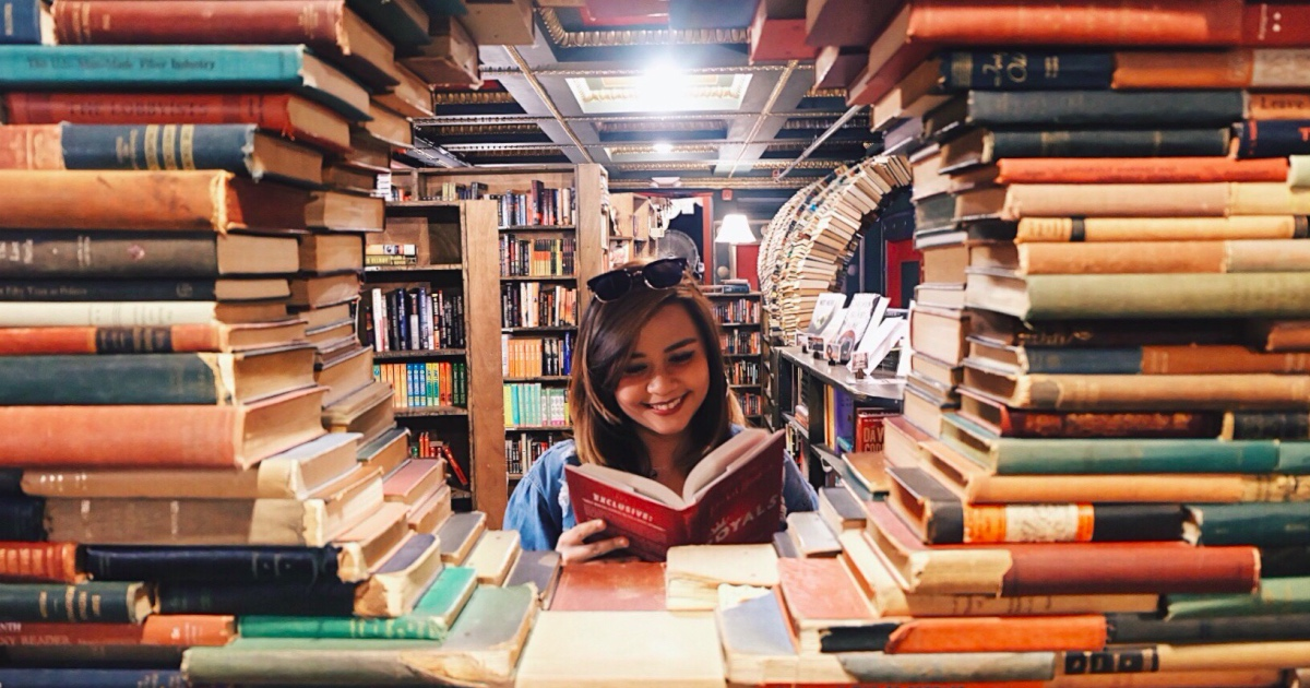 Woman surrounded by stacks of library books