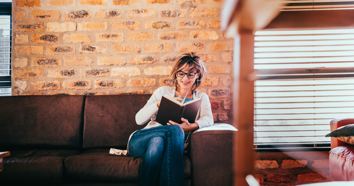 Smiling woman reading a book at home on couch in living room