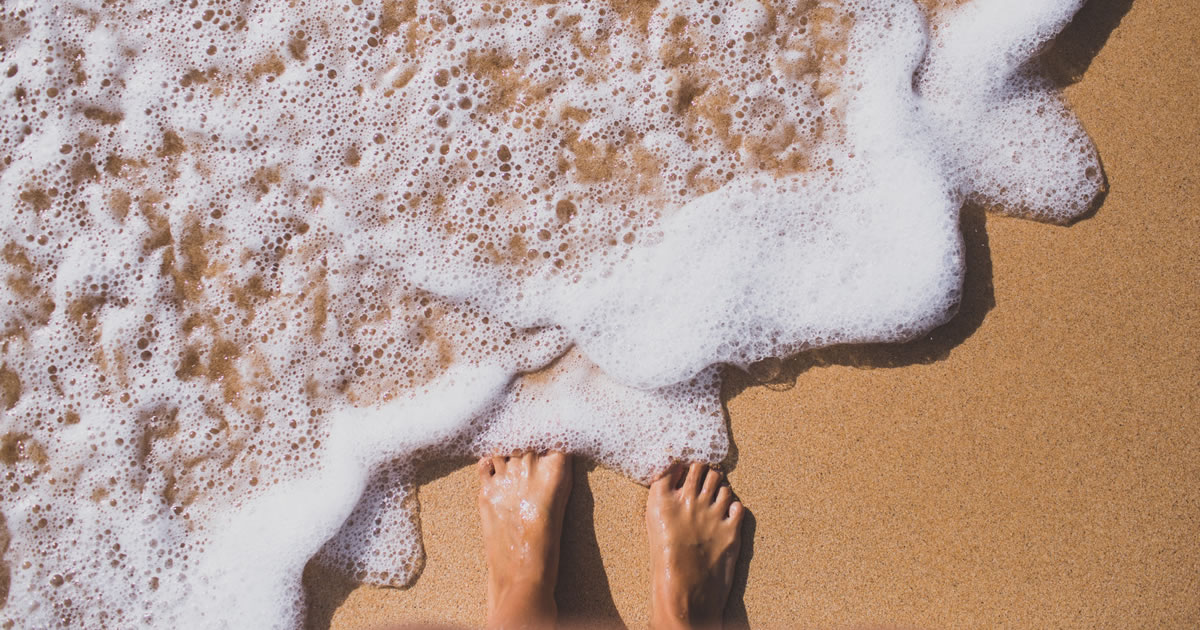 Seafoam partially covering bare feet on a sandy beach