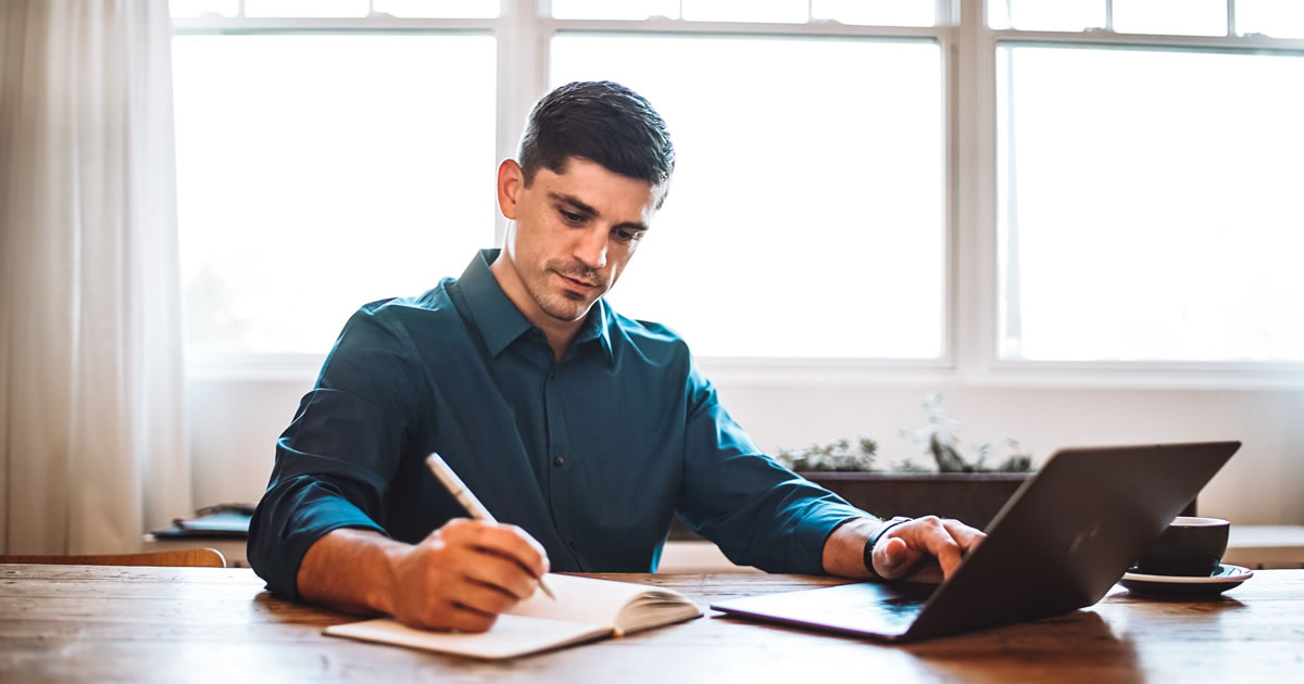 Man at desk working on laptop and writing in notebook