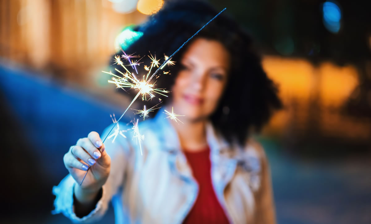 Woman holding sparkler at night on illuminated street