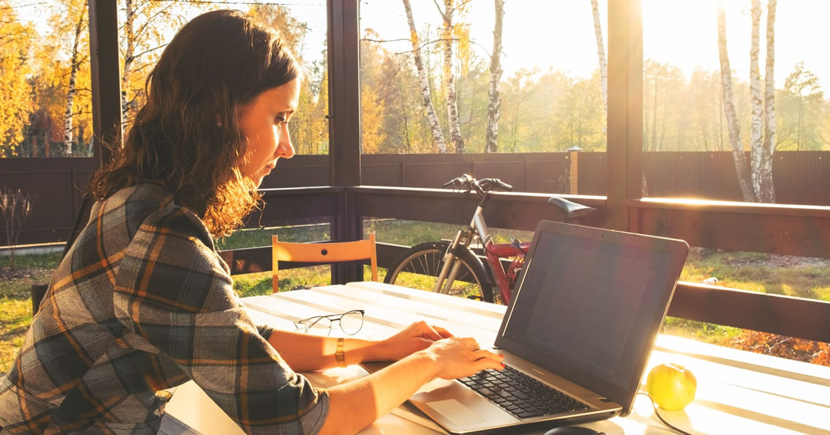 Young businesswoman writing on laptop from home office screened porch
