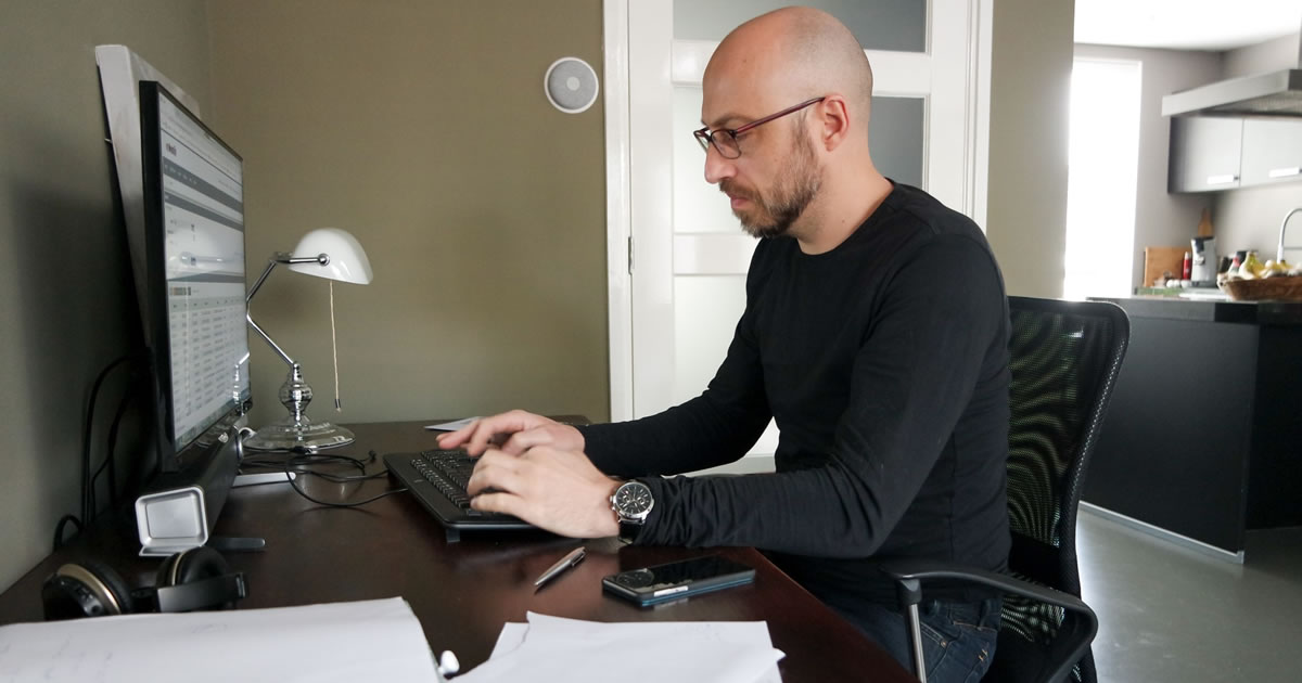 Man writing on computer at desk at home