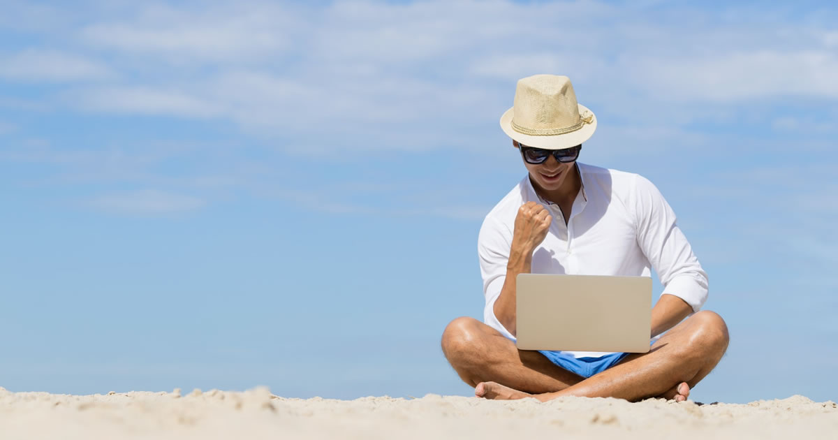 Young man writing on his laptop while sitting on a beach with a blue sky background
