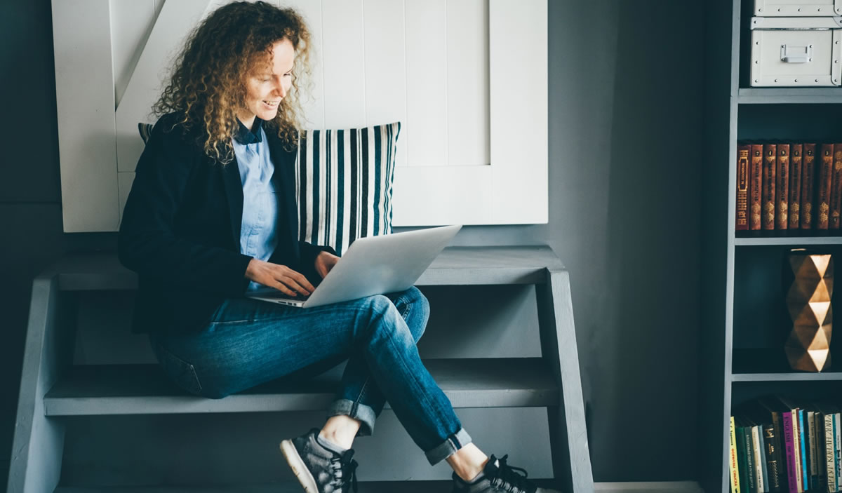 Young woman writing on laptop in apartment