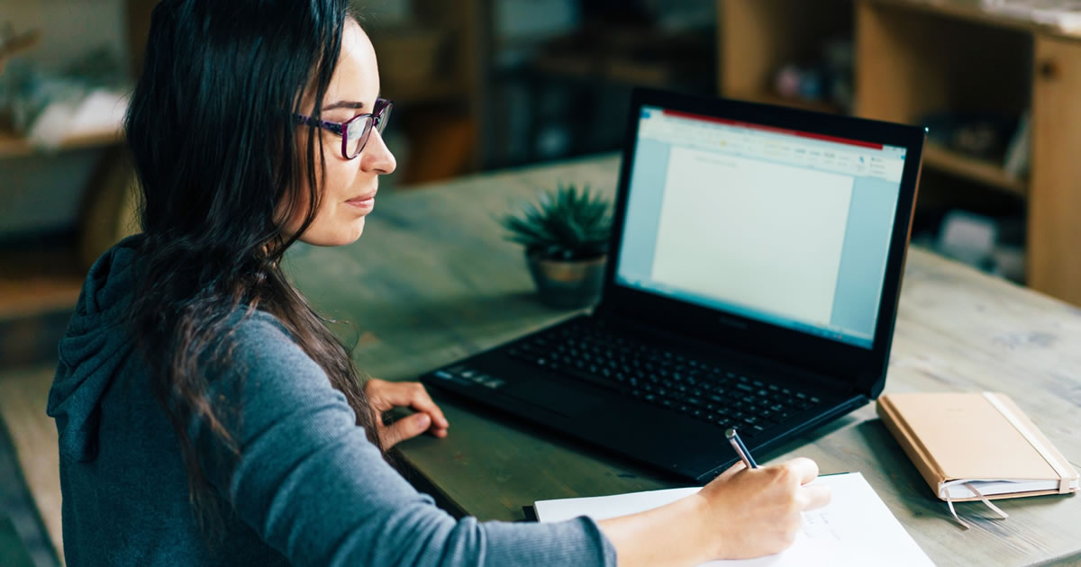 Woman writer working on laptop at desk