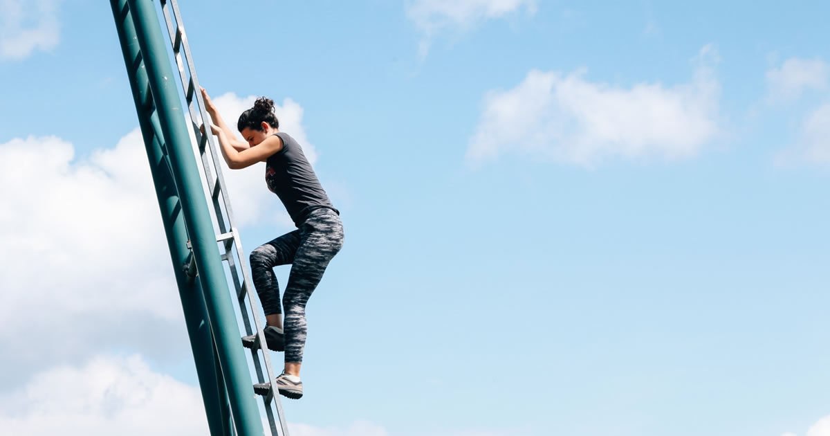 Woman climbing up a metal ladder