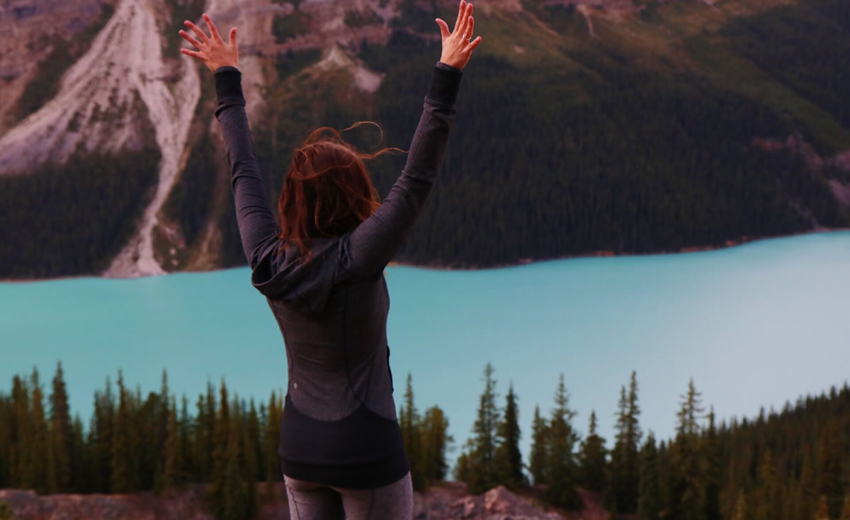 Woman standing outdoors facing away with her arms stretched above while looking at trees, mountains, and water