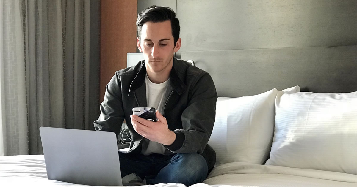Young man sitting on bed checking smartphone and writing on laptop
