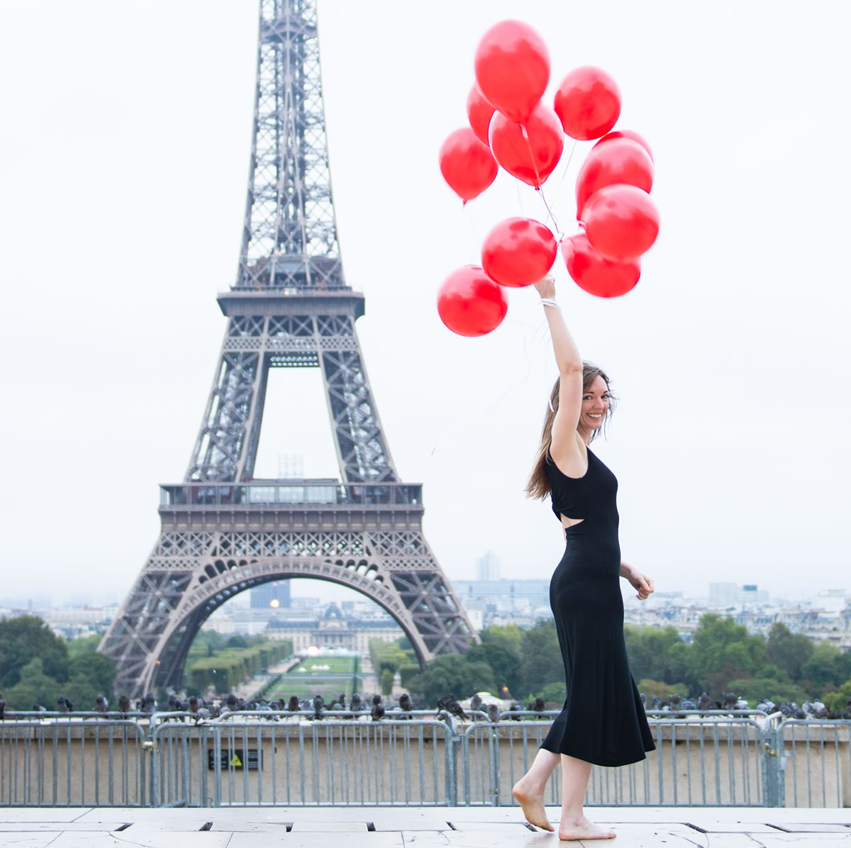 Copywriter Bonnie Caton holding red balloons while overlooking the Eiffel Tower at sunrise at the Trocadero in Paris