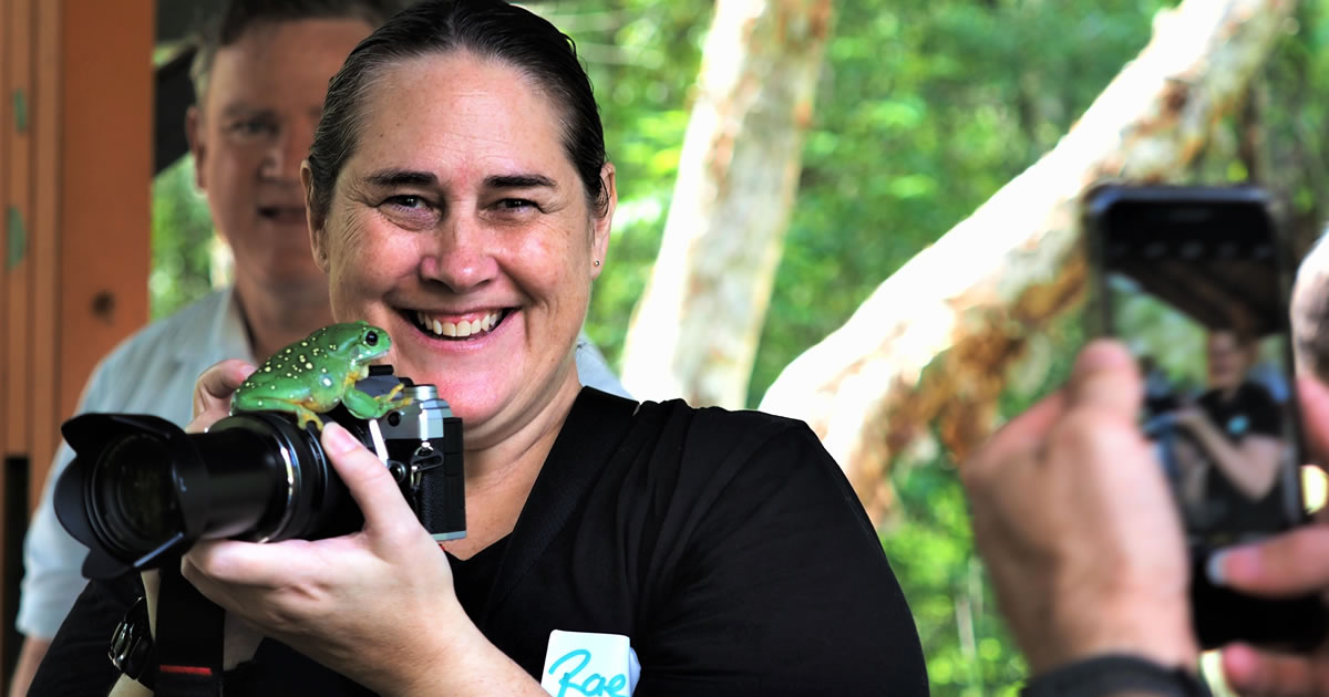 Photo of copywriter Rae Brent laughing at the sight of a small frog on her camera