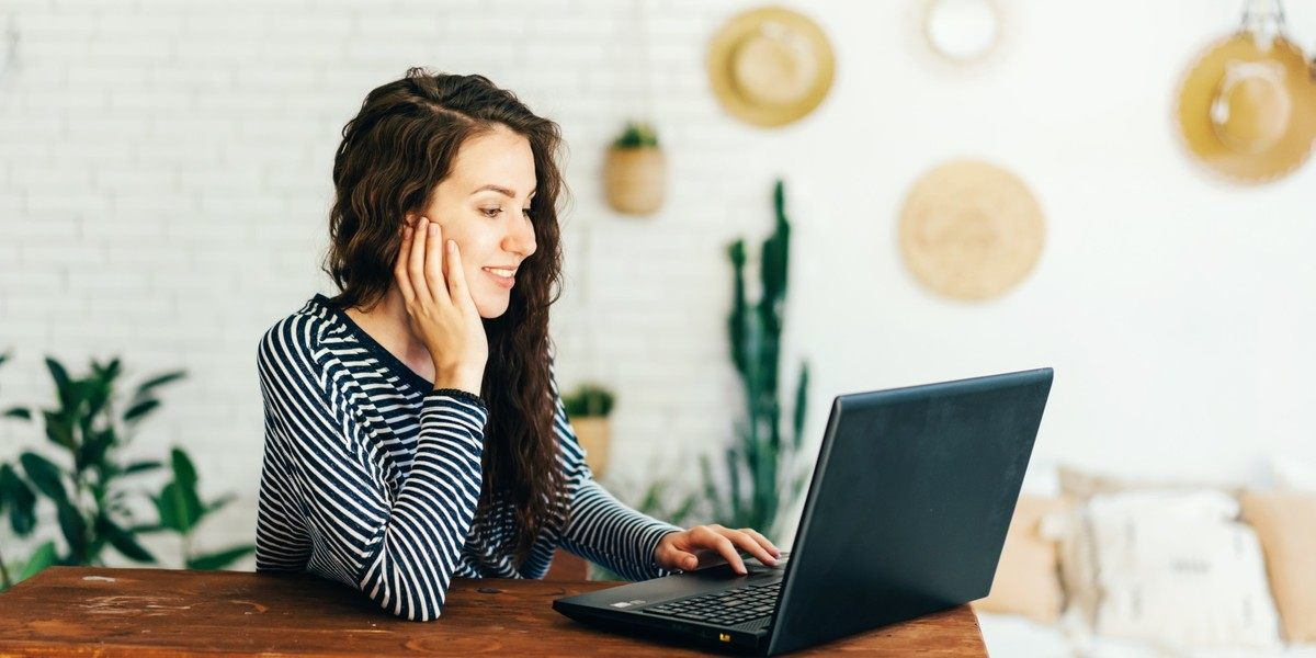 Woman writing on laptop at home