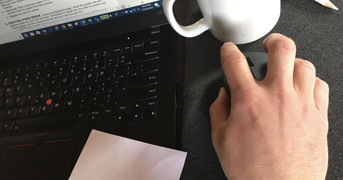 Closeup of desk with man's hand using computer mouse next to laptop and coffee