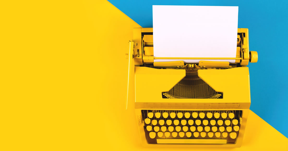 Yellow typewriter on yellow and blue background
