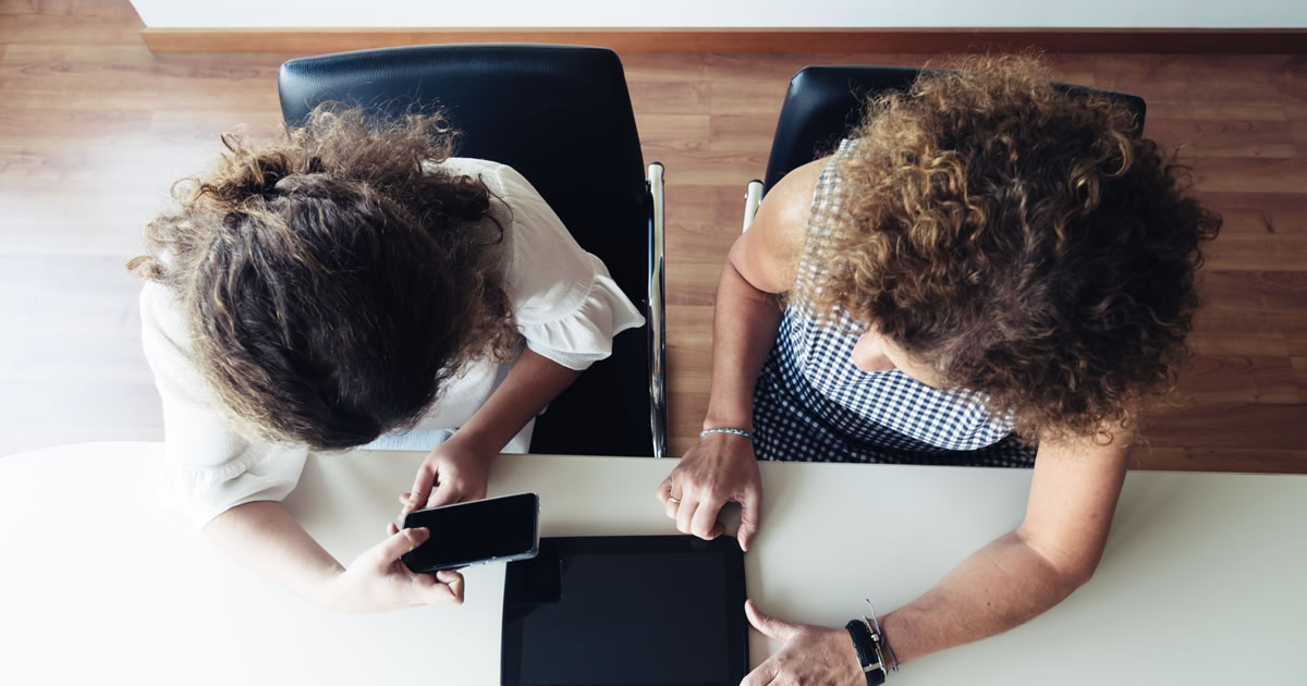 Overhead view of two businesswomen with smartphone and tablet working at office table together
