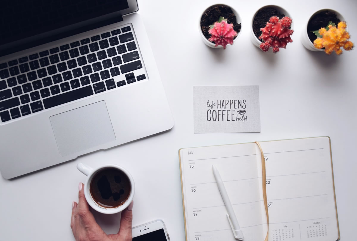 Overhead shot of a desk with a laptop computer, mobile phone, weekly planner, coffee cup, and a card saying LIFE HAPPENS COFFEE HELPS