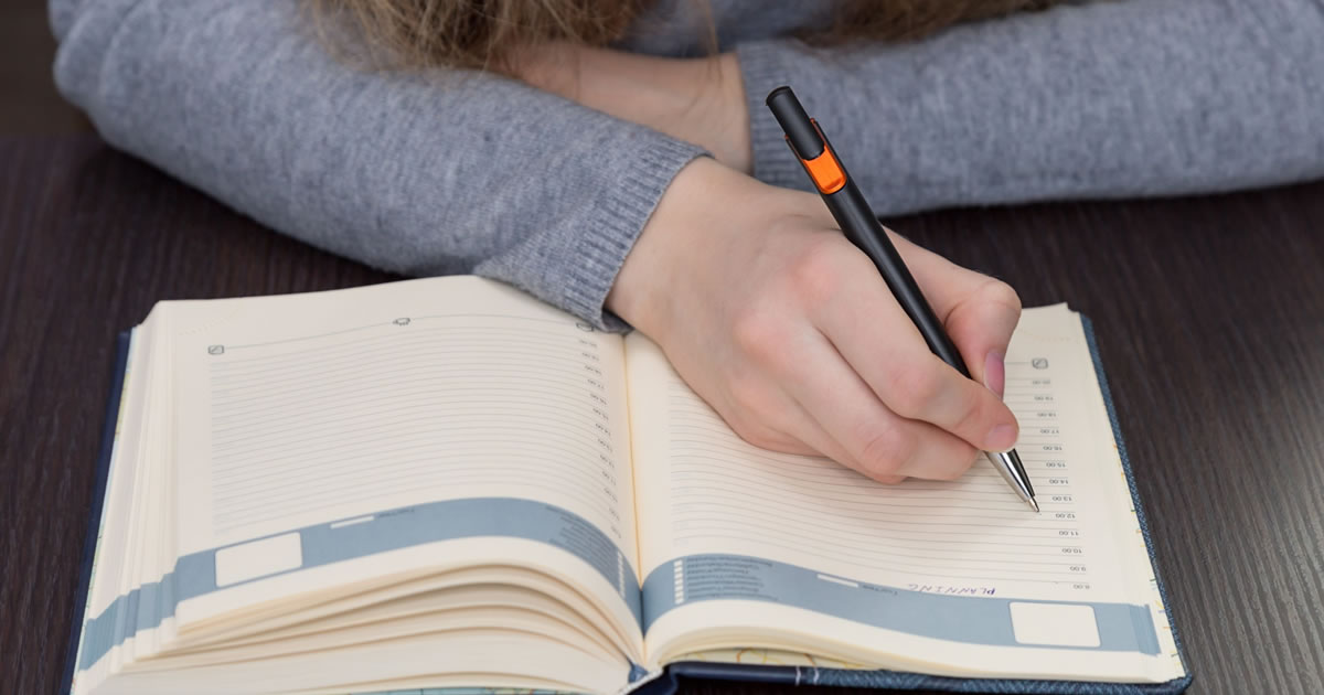 Girl writes a plan for the day in her diary