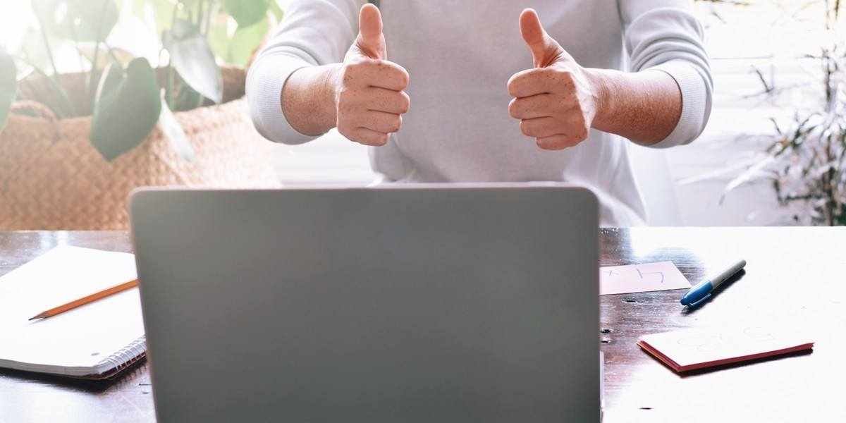 Man giving thumbs up and encouraging someone on computer