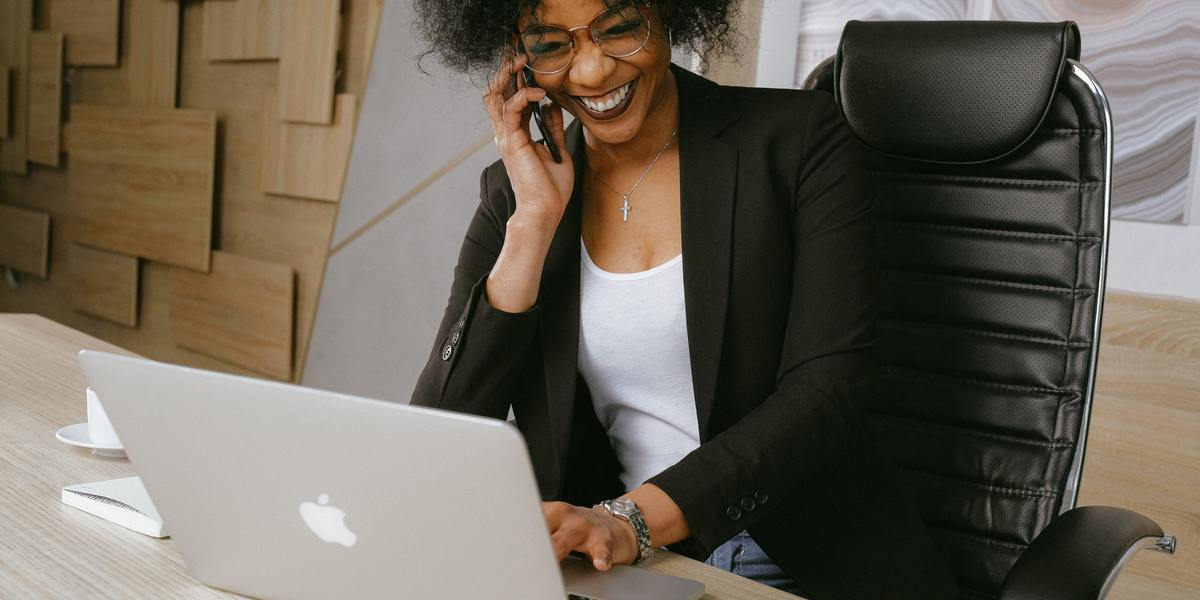African American smiling young woman writing on laptop and talking to a client over the phone