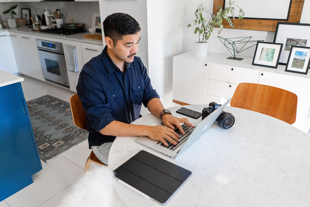 Professional entrepreneur writing on his laptop at home