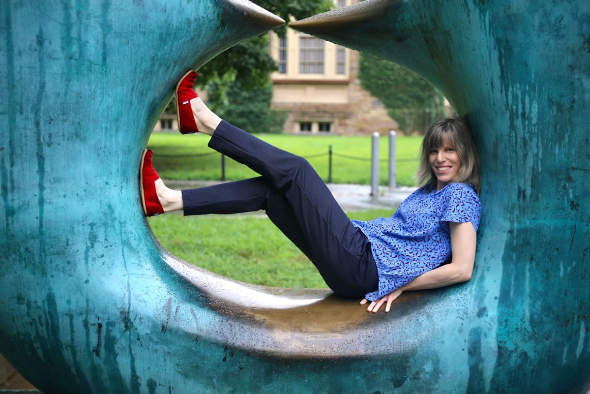 Jessica McKay laying in a large circular sculpture in a park
