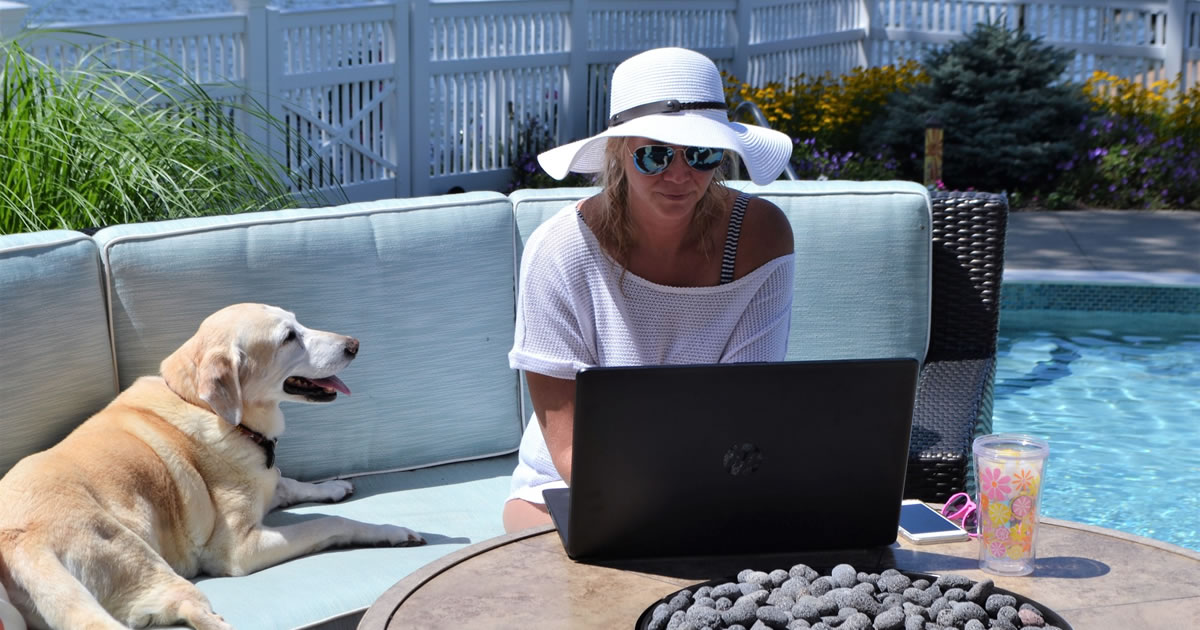 Woman writing on her laptop at the pool with her dog keeping her company