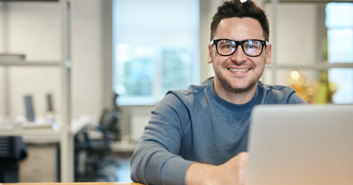 Smiling male writer sitting at table with laptop