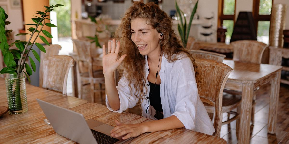 woman sitting on a chair in a video call on a MacBook laptop