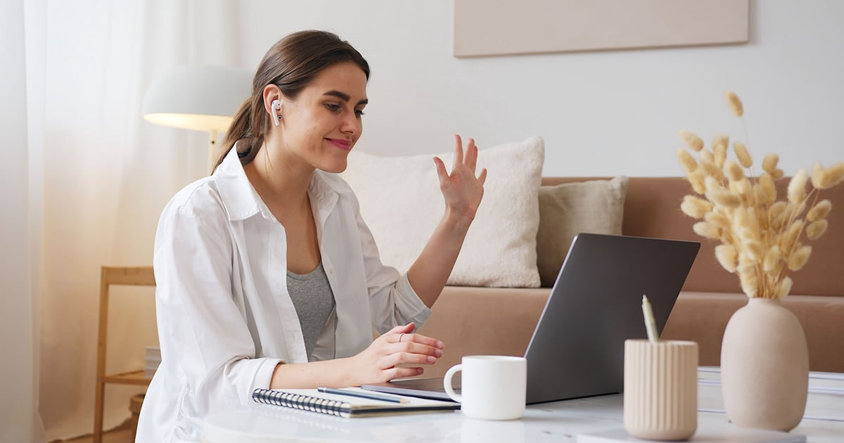 Cheerful woman writer having video meeting via laptop