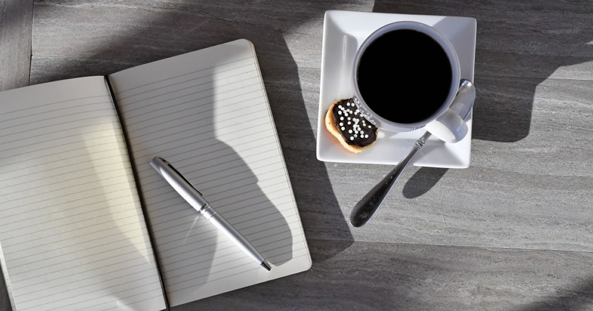 Blank journal, pen, pastry, and full coffee cup
